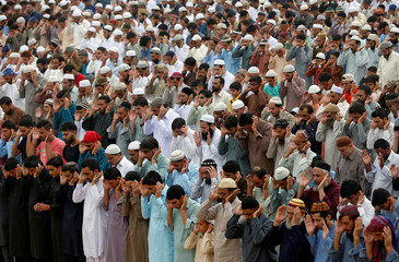 Men attend Eid al-Fitr prayers to mark the end of the holy fasting month of Ramadan at a play ground in Karachi