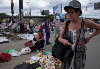 A woman looks at goods at a flea market in Kiev