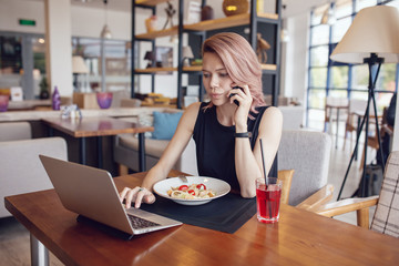 Business woman eats at a cafe and uses a smartphone and laptop.