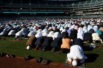 Muslims pray on the baseball field for the celebration of the Eid al-Fitr holiday, the end of the holy month of Ramadan at Angel Stadium of Anaheim in Anaheim, California