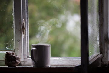 Mug of hot tea standing on the window. Reflection, calm, relax