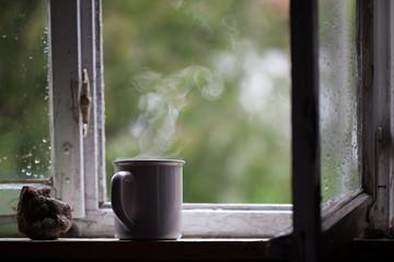 Mug of hot tea standing on the window. Reflection, calm, relax