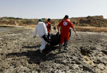 Rescuers carry a bag containing the dead body of a migrant at the coast of Tajoura