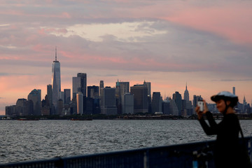 A woman photographs the sunset in the Brooklyn borough of New York