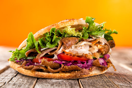 Close up of kebab sandwich on old wooden table.