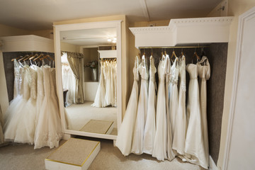 Rows of wedding dresses on display in a specialist wedding dress shop. Bridal boutique.