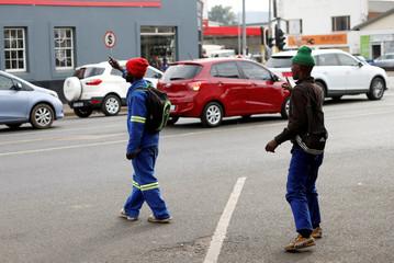 Unemployed men gesture in the hope of getting work in Pietermaritzburg