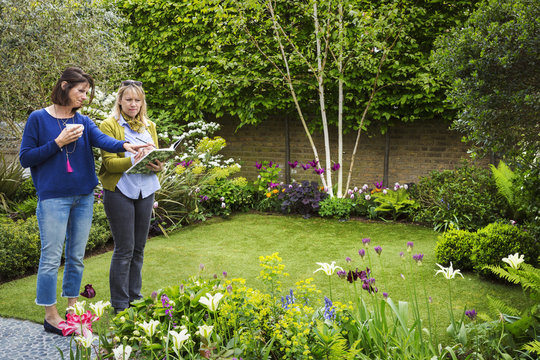 Two women standing in a garden on a lawn surrounded by flowerbeds, discussing garden design.