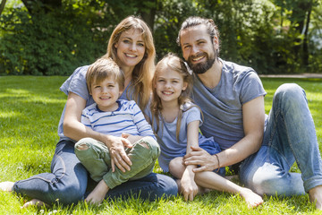 Portrait of happy family sitting on meadow