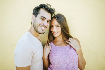Smiling couple looking at camera in front yellow wall