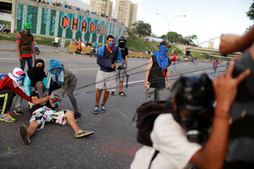 Demonstrators use a giant sling shot while clashing with riot security forces during a rally against Venezuela's President Nicolas Maduro's Government in Caracas