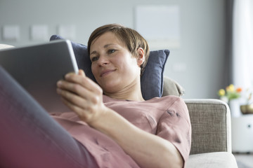Portrait of smiling woman lying on the couch using tablet