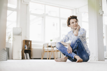 Woman sitting on floor in her apartment