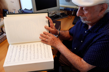 Lebanese calligrapher, Mahmoud Bayoun, turns the pages of the Koran that he wrote in Diwani font, at his office in Beirut