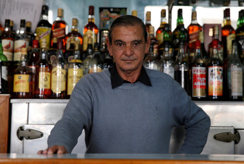 A bartender poses for a picture at a bar in Montevideo, Uruguay