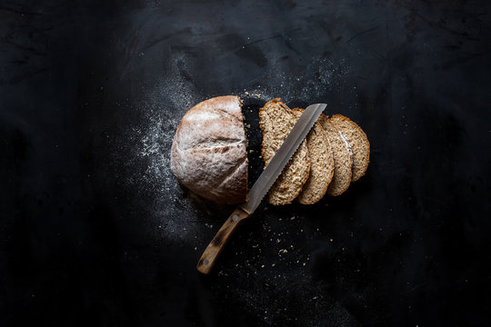 Sliced bread and a knife lying on a black metal table