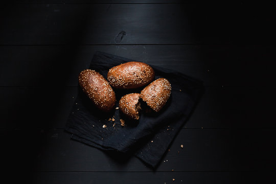 Bread lays on a black table on a dark tablecloth. Low key.