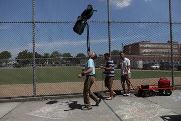 Furman attempts to set the Guinness World Record for the farthest distance walked while balancing a powered lawnmower on the chin in Queens
