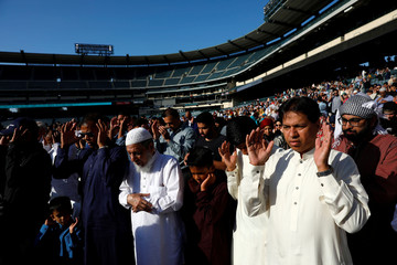 Muslims pray during the celebration of the Eid al-Fitr holiday, the end of the holy month of Ramadan at Angel Stadium of Anaheim in Anaheim, California
