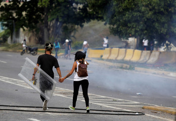 A couple walks while holding hands during a rally against Venezuela's President Nicolas Maduro's Government in Caracas