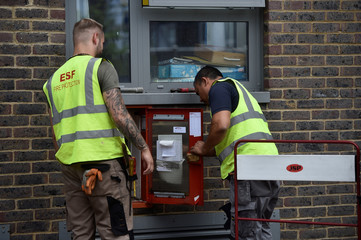Workmen inspect safty equipment at the Dorney Tower residential block, after residents were evacuated as a precautionary measure following concerns over the type of cladding used on the outside of the buildings on the Chalcots Estate in north London