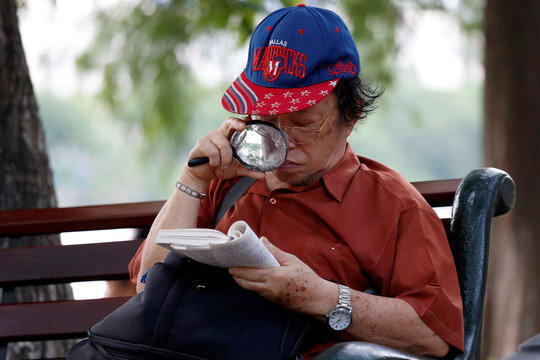 74 years old retired colonel Phan Tu Hai uses a magnifying glass to read a book near Hoan Kiem lake in Hanoi