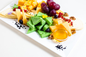 Different sorts of cheese, sliced, red grapes, walnuts, honey in a bowl, red currant, green cheese, wooden stand, goat and cow cheese, square, triangular pieces of appetizing
