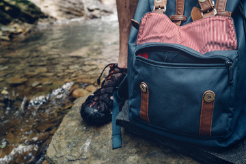 Adventure Hiker Man Feet, Backpack And Thermos On Waterfall Background Closeup Journey Hiking Travel Concept