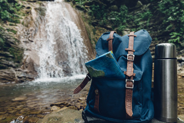 Hipster Blue Backpack, Map And Thermos Closeup. View From Front Tourist Traveler Bag On Waterfall Background. Adventure Hiking Concept