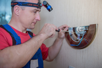 Male electrician connects the lamp on the wall