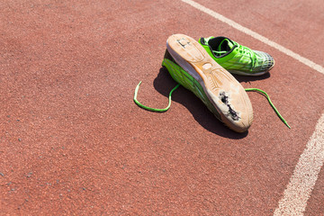 A pair of broken green running shoes with big holes in the sole laying on a running track