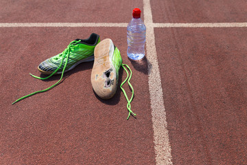 A pair of broken green running shoes with big holes in the sole laying on a running track besides a water bottle.