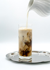 pouring milk into a glass of coffee