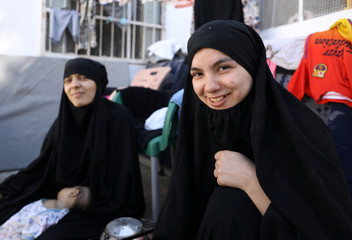 Lebanese Nour al-Huda and Tunisian Iman Othman, wives of former Islamic State fighters, sit at a camp for displaced people in Ain Issa