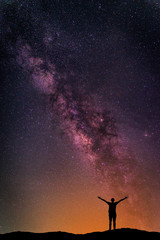 Wall Mural - Landscape with Milky way galaxy. Night sky with stars and silhouette happy man on the mountain. Long exposure photograph.