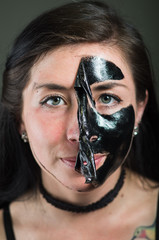 Close up of a beauty young woman taking off half of a black face mask