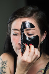 Close up of a beauty young woman taking off a black face mask