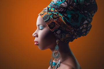 young beautiful fashion model with traditional african style with scarf, earrings and makeup on orange background.