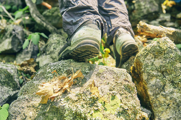 Shoes of a hiker climbing up the rocky mountain