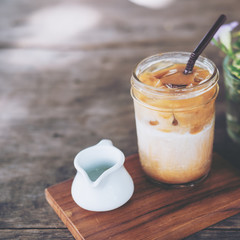 A glass of Iced coffee on wooden table in vintage cafe