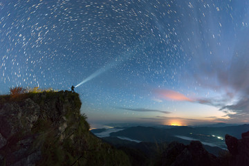 Star trail over the mountain with the man light up the sky before sunsire, Nan Province, Thailand Wall mural