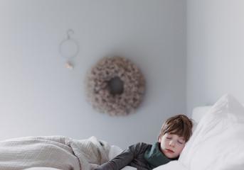 Junge liegt mit Fieber im Bett