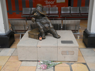 A jar of marmalade and a bunch of flowers are left at the foot of a Paddington bear statue at Paddington station, London