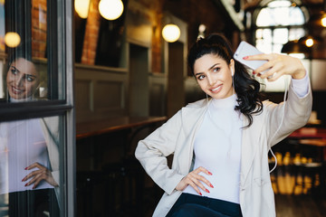 Cheerful brunette woman in white elegant clothes holding generic mobile phone making sefie against cozy cafe background. fashionable young female making photo of herself having fun. Modern technology