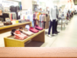 Empty wooden table space platform and abstract blur and defocused clothing department in shopping mall and retail store interior for background.