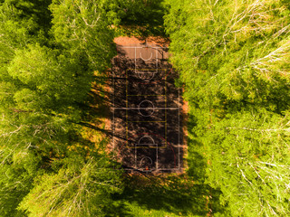 Aerial view of basketball field on day time in forest. Above with drone.