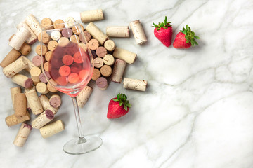 Rose wine with corks, strawberries, and copy space