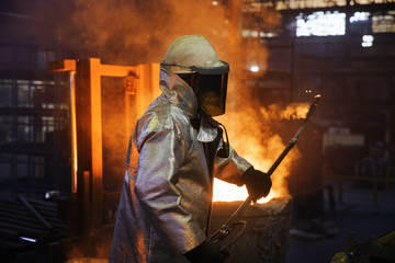 Foundry Worker Checks Temperature Of Molten Metal In Steel Mill