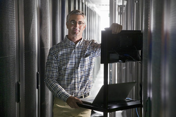 Portrait Of Technician With Laptop Working In Secure Data Centre