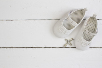 Christening background with white baby booties and crystal cross isolated on white wooden plank floor